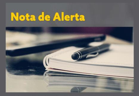 caneta sobre caderno e título em amarelo Nota de Alerta