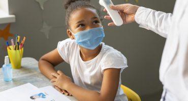 Criança negra em sala de aula tendo a sua temperatura medida
