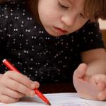 criança com sindrome de down escrevendo