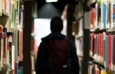 aluno no meio de livros em uma biblioteca