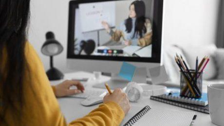 garota sentada de frente para a tela do computador assistindo video conferencia