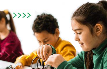 Três crianças sorridentes sentadas em uma mesa interagindo com materiais da aula de robótica.
