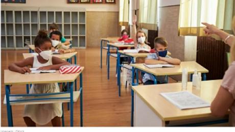 perfil de professora apontando para alunos, sentados nas carteiras dentro da sala de aula