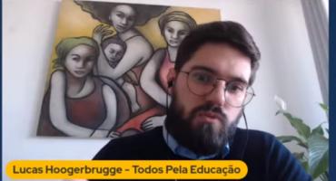 Print de videoconferência com homem branco, usando óculos de grau. Atrás dele um quadro com pintura de três mulheres.