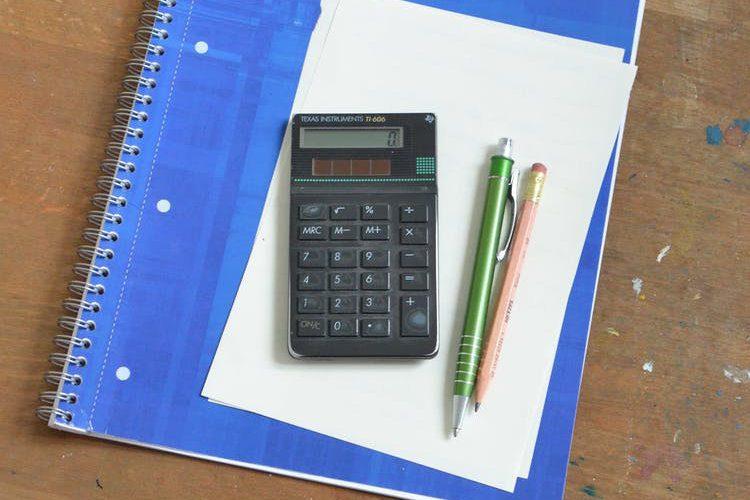 Calculadores, lápis e caneta sobre um caderno encima da mesa