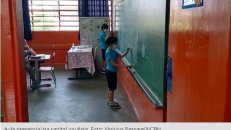 duas crianças na sala de aula escrevendo no quadro verde