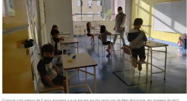 Crianças na sala de aula, sentadas nas carteiras, e professora em pé no meio da sala