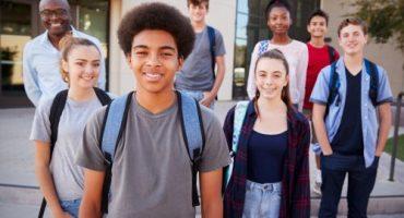 Foto de 7 jovens negros e brancos, com mochilas nas costas, e um homem negro. Todos olham para a foto e sorriem.
