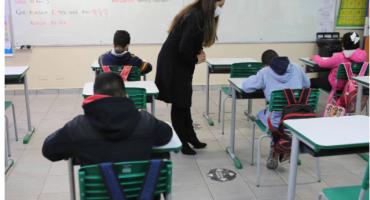 alunos na carteira e professora na sala de aula em escola