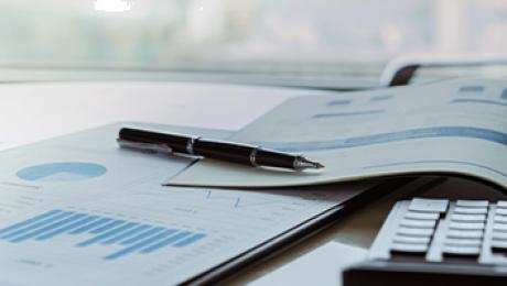 Foto de mesa com papéis de gráficos, caneta e calculadora