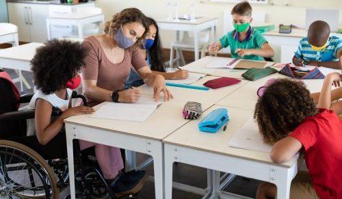 Foto de professora sentada a uma grande mesa com alunos ao redor, todos usam máscara cirúrgica. Uma aluna está em cadeira de rodas.